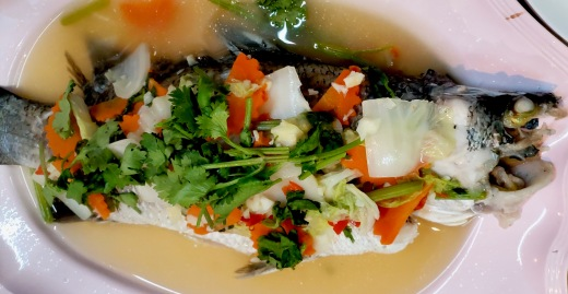 A large steamed fish with common Thai Veggies